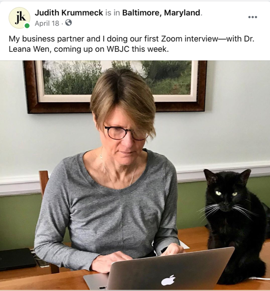 "Facebook post reads: ""My business partner and I doing our first Zoom interview—with Dr. Leana Wen, coming up on WBJC this week."" Krummeck pictured at computer with her cat."